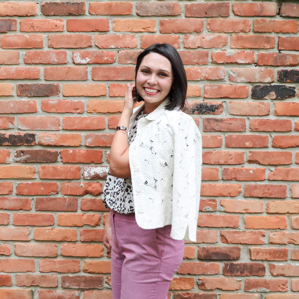 Nicole Parker, PhD, LMFT professional counselor smiling and standing in front of a brick exterior wall