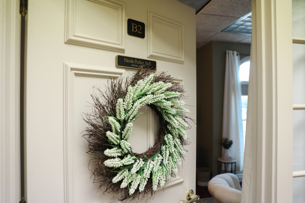 Interior shot of office door with a summer wreath for the office of Nicole Parker, PhD, LMFT